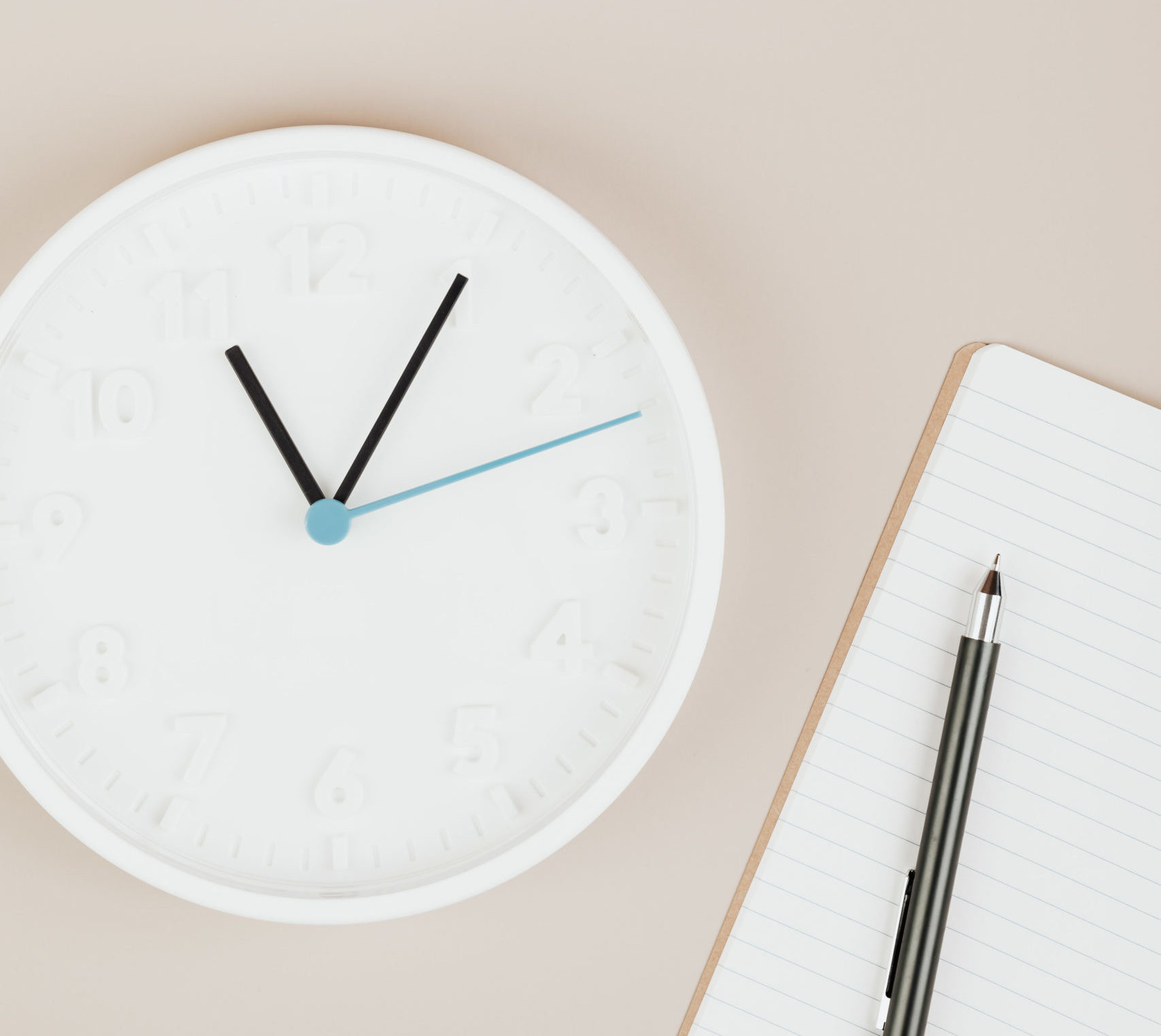 Picture of a clock beside a notepad and pen