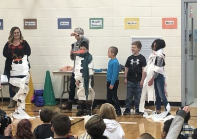 Third grade teachers leading students in a fun minute-to-win-it game.