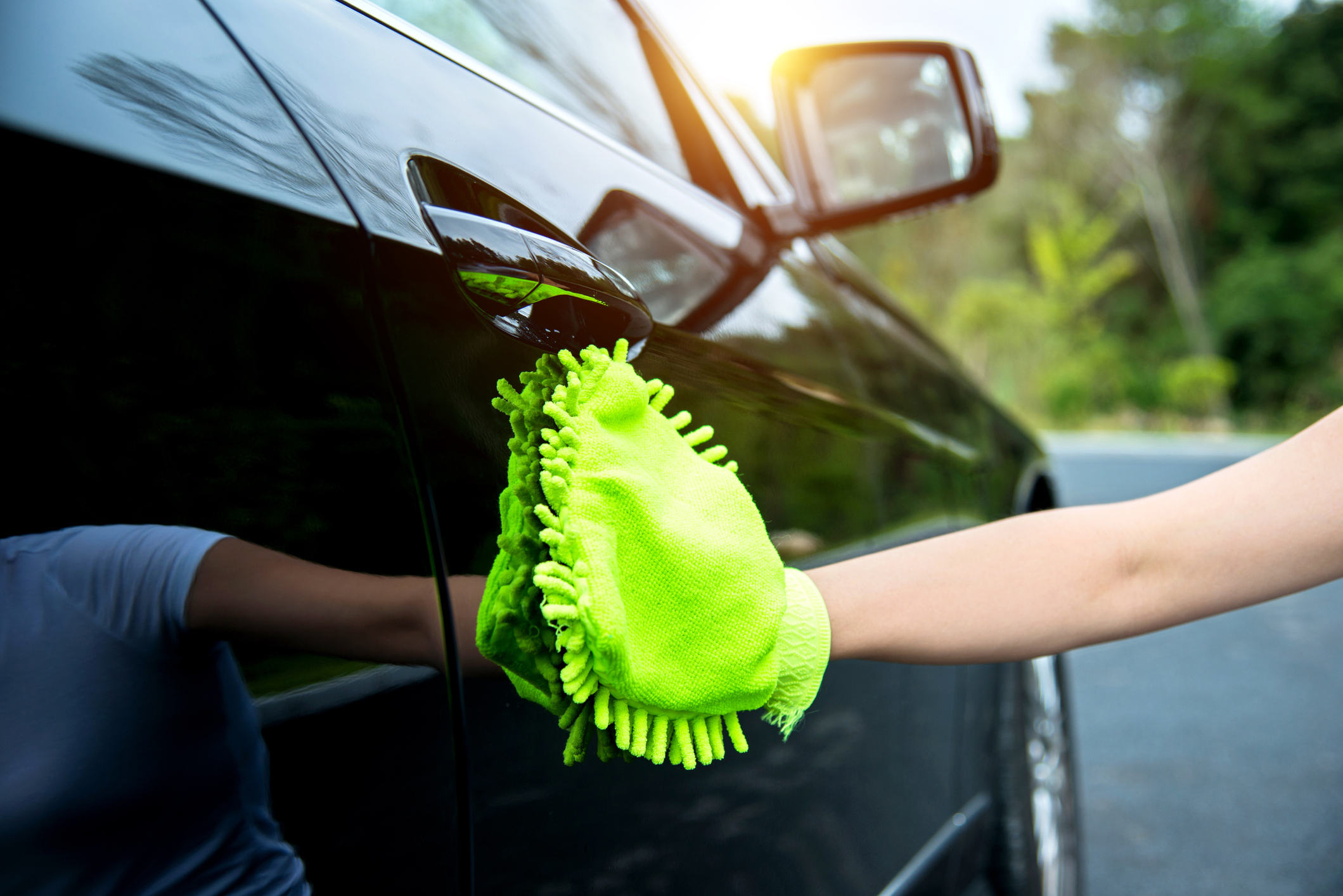 Woman hand polishing her black car