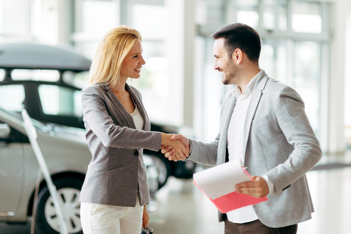 A man shaking a woman's hand in a dealership.