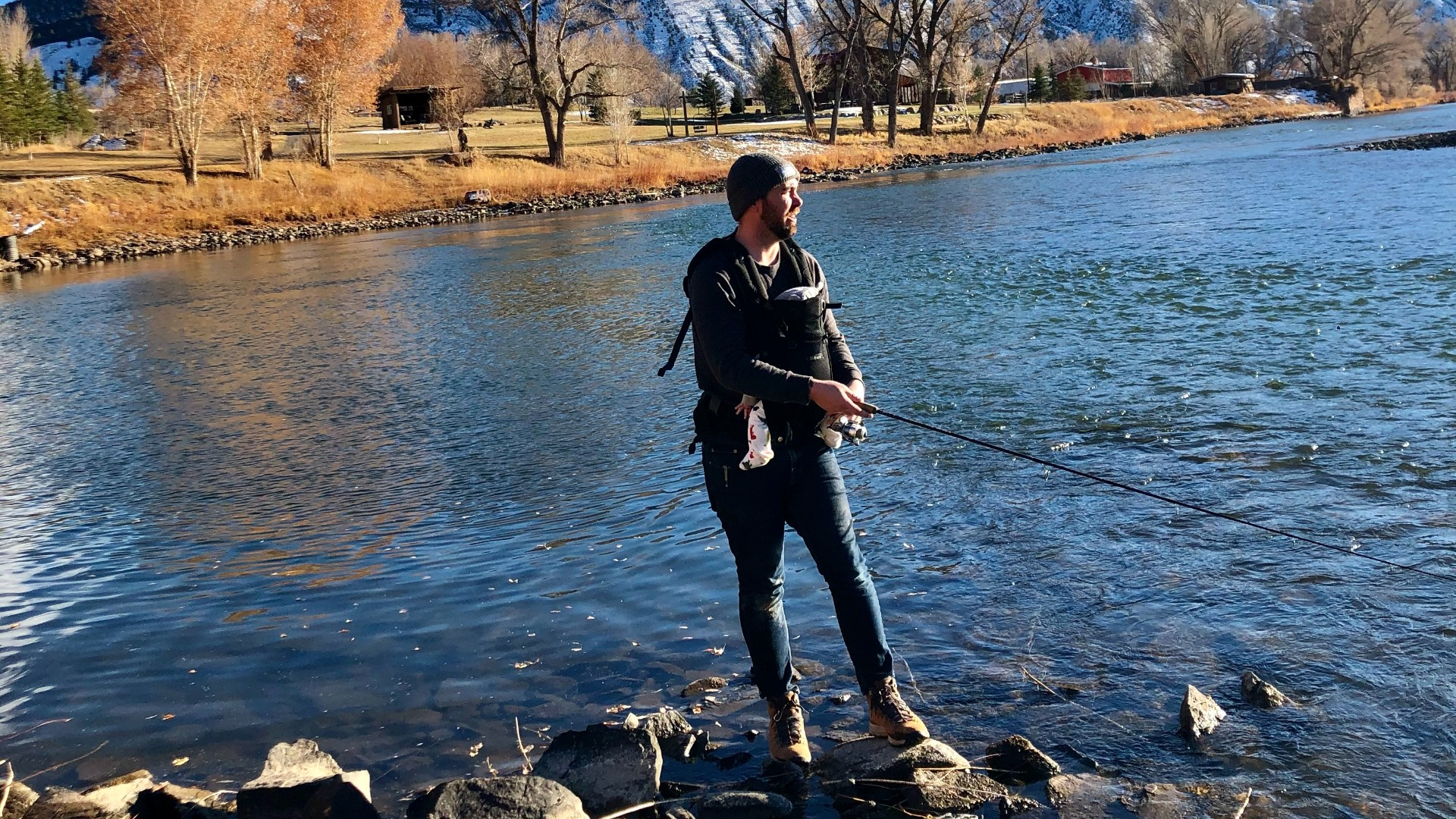Boots in the icy water, baby in tow, fishing like a boss.