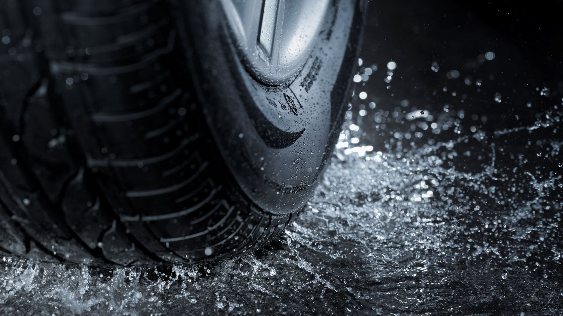 A detailed view of a tire's tread and sidewall as it splashes through water.