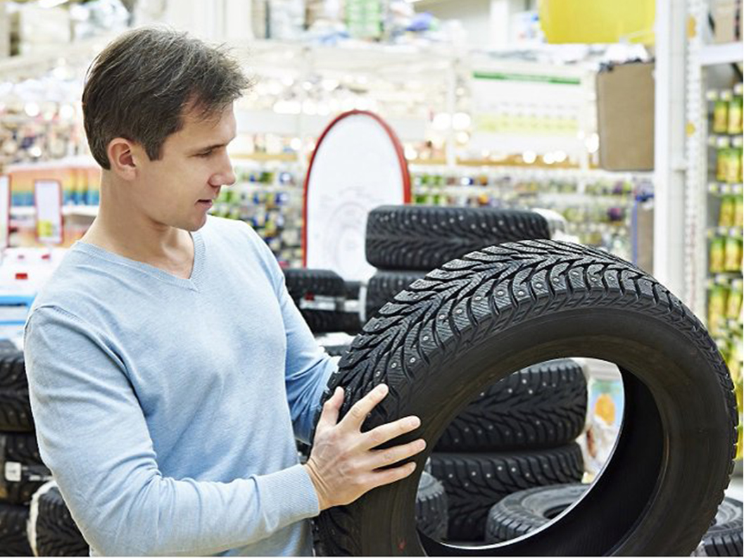 man inspecting tire at store