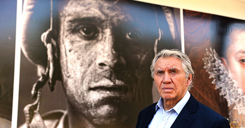 Vietnam War photojournalist Don McCullin in front of Louie Palu's portrait of Sgt. Carlos Orjuela.