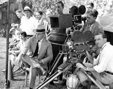 """D. W. Griffith (with hat) under camera. Struss behind the lens, same camera """"Drums of Love,"""" 1928."""