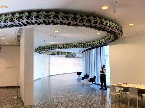 """""""Snake Ceiling,"""" an installation of children's backpacks."""