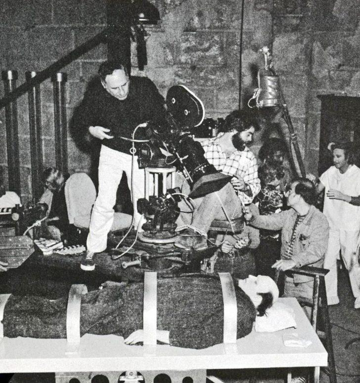 Shooting Young Frankenstein (1974), director Mel Brooks angles the camera on actor Peter Boyle as Hirschfeld (on ladder, at right) confers with his crew.