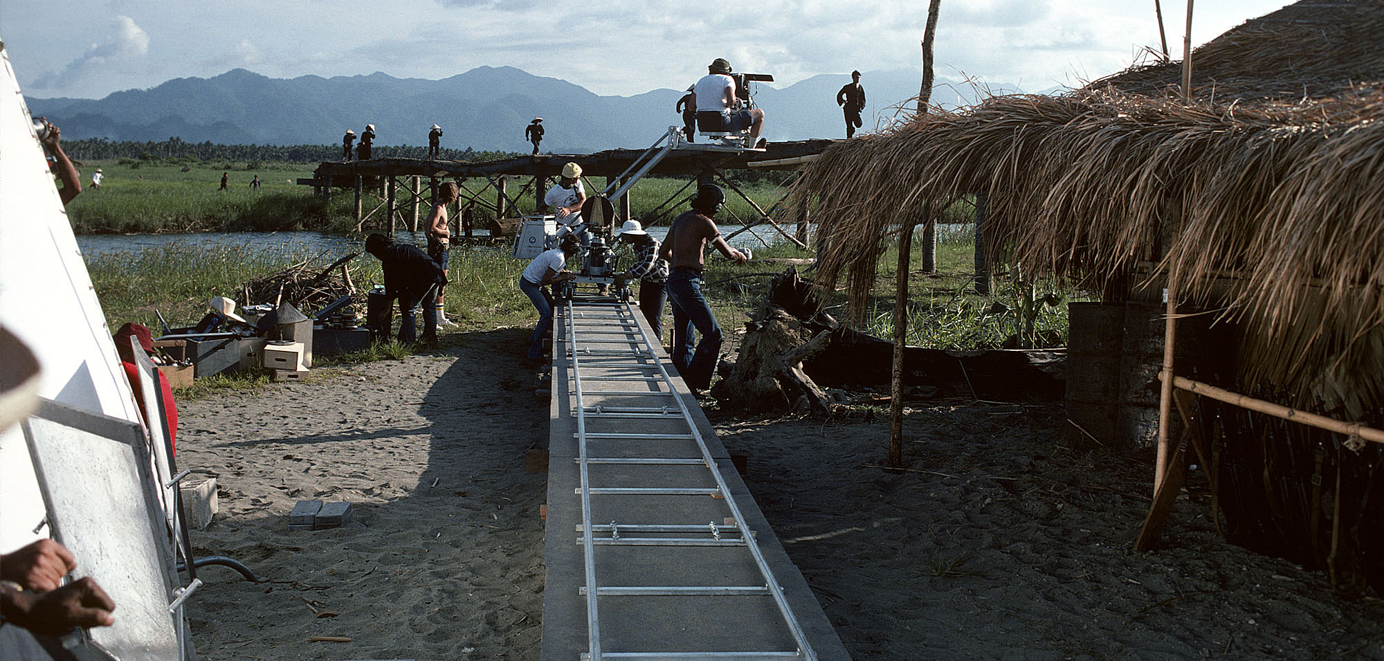 The crew dollies in on Viet Cong soldiers while filming the aerial assault.