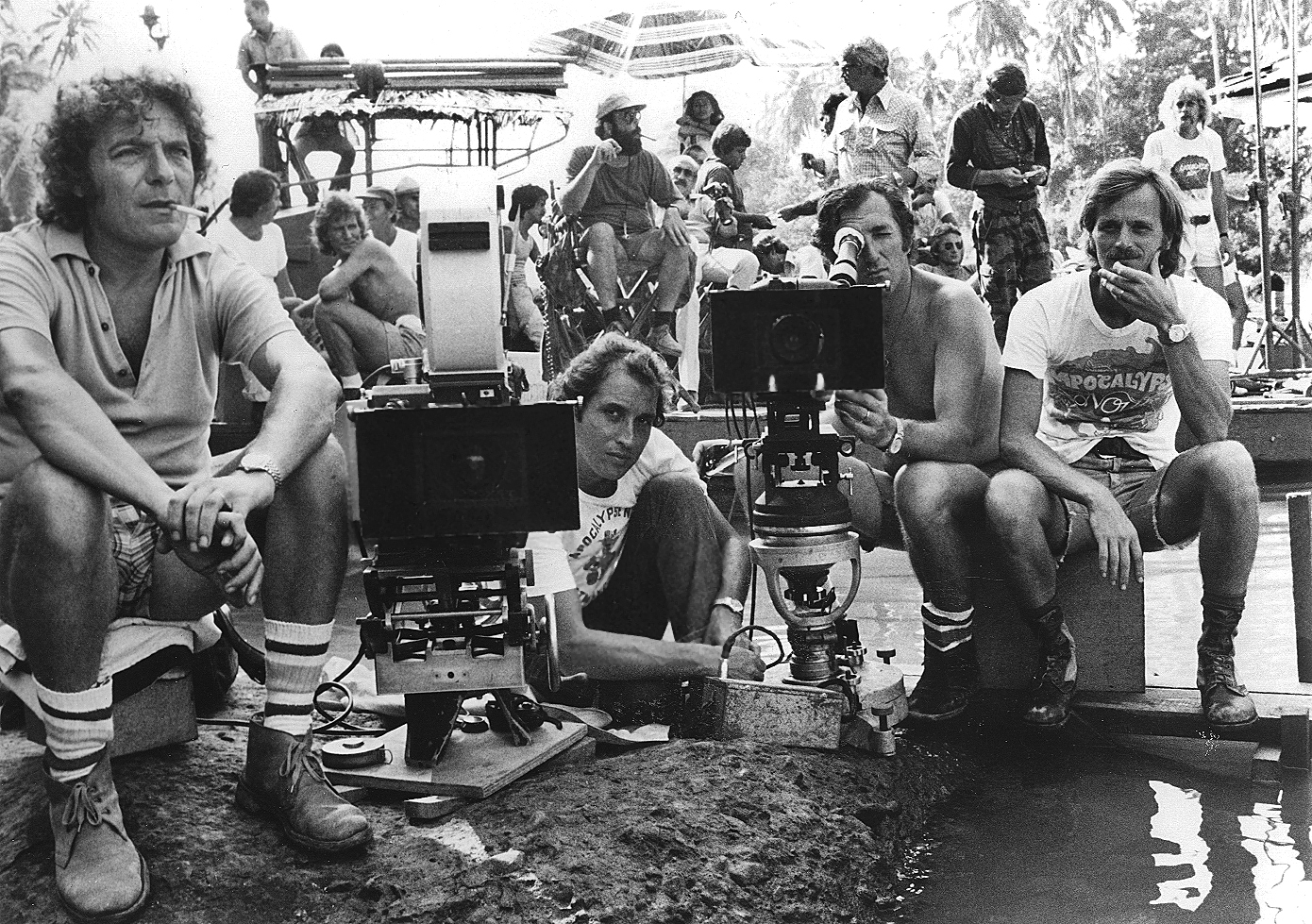 Storaro (kneeling at center) and his crew set up two cameras. Flanking him (from left) are camera assistant Rino Bernardini, operator Enrico Umetelli and camera assistant Mauro Marchetti. In the background, Coppola (seated) chats with AD Jerry Ziesmer (white shirt) as Dennis Hopper (in camo pants) stands by.
