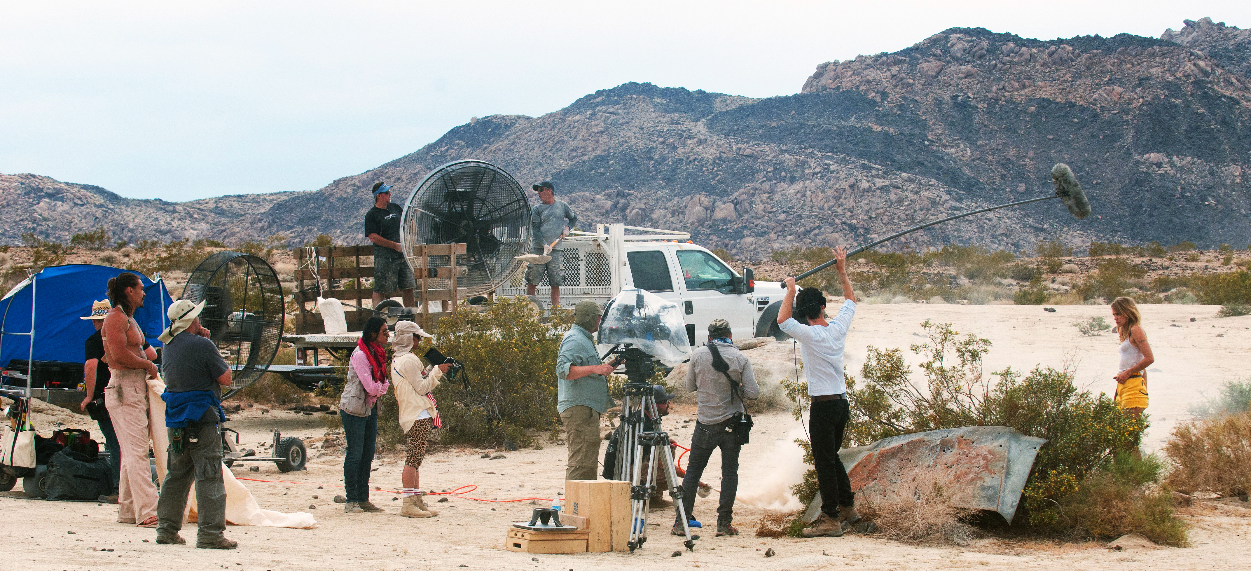 Waterhouse, Momoa, Amirpour (wearing cap and holding director's monitor) and crew capture a scene on location. Ritter fans are ready to provide clouds of dust.