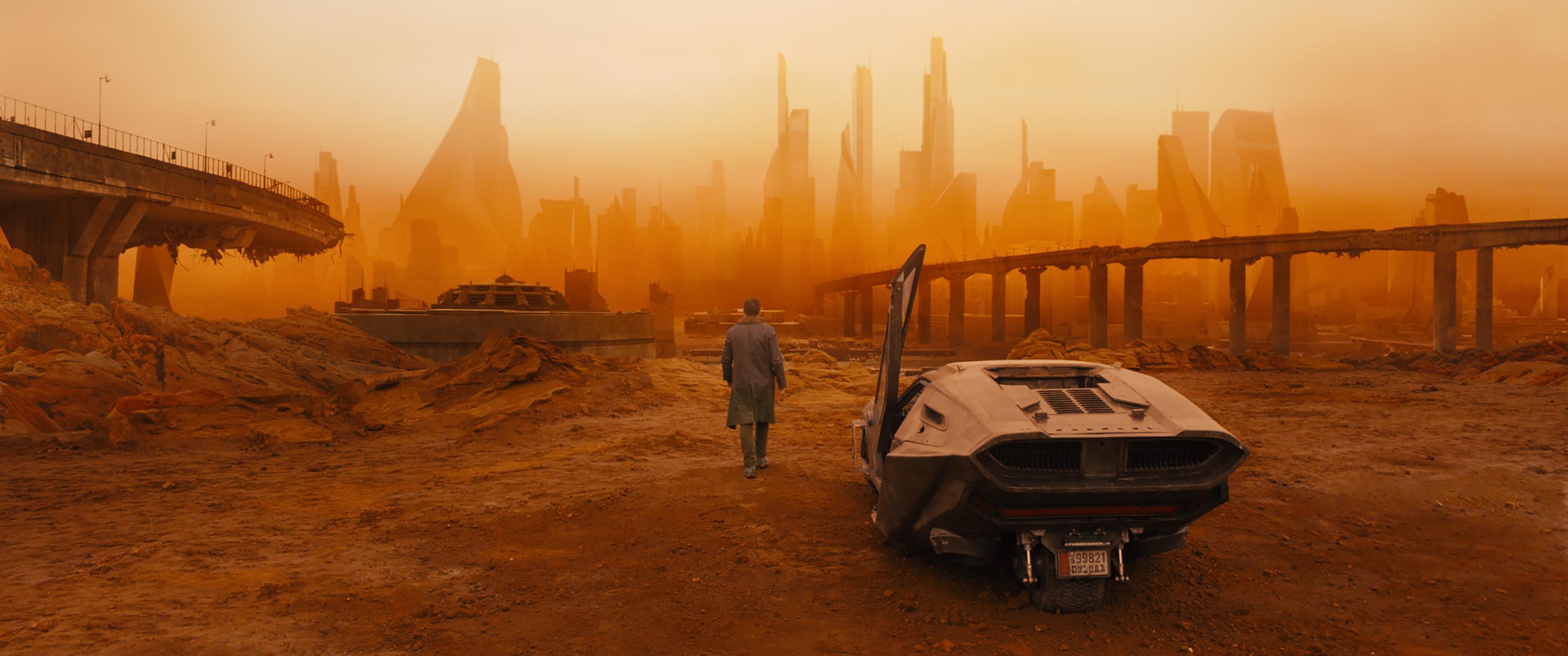 "K (Ryan Gosling) steps away from his ""spinner"" car toward a bleak and brutal landscape."