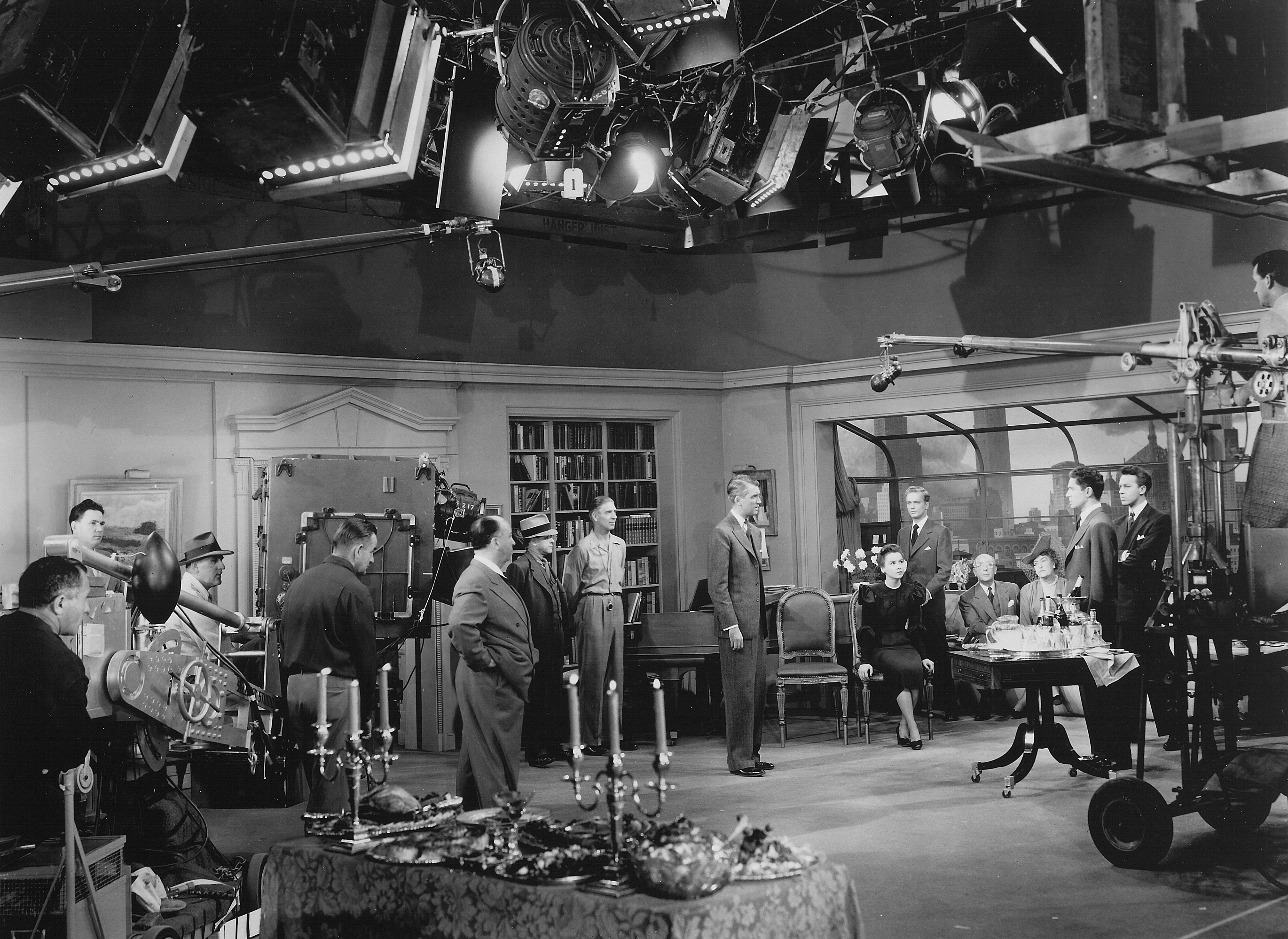 Hitchcock and his camera crew — including ASC members Joseph A. Valentine and William V. Skall (standing in front of camera) — rehearse to shoot one of the 10 lengthy shots (up to 10 minutes each) seen in the thriller Rope (1948), which was written, choreographed, photographed and edited to appear to be one single, continuous shot taking place in real time. This was also the director's first Technicolor project.