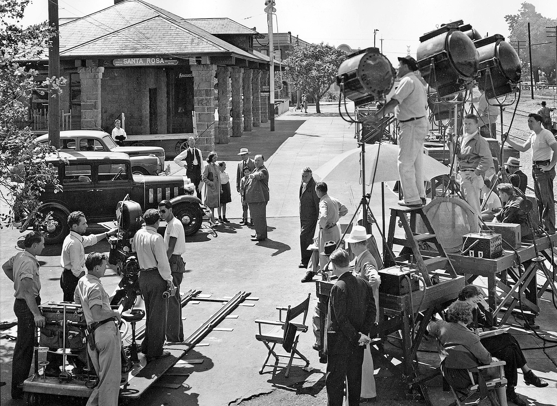 Hitchcock (center, pointing) and his production crew descended on the sleepy town of Santa Rosa, California, to shoot his thriller Shadow of a Doubt (1943), starring Teresa Wright and Joseph Cotten. Photographed by Joseph A. Valentine, ASC — who had previously shot Saboteur (1942) for Hitchcock — the picture was said to be the director's favorite. He and Valentine (seen here behind the camera, holding a viewfinder) would later collaborate on Rope (1948).