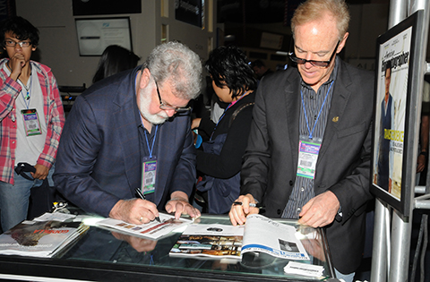 Cundey and ASC President Richard Crudo autograph copies of AMERICAN CINEMATOGRAPHER.