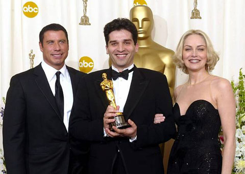 """Danis Tanovic, flanked by John Travolta and Sharon Stone with his Oscar for """"No Man's Land,"""" 2001."""