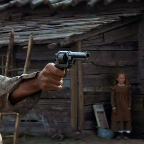 Munny (Clint Eastwood) practices his marksmanship as his children look on.