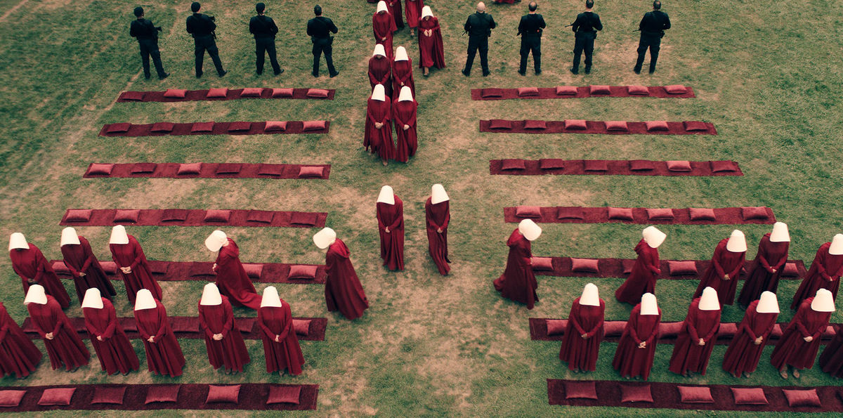 A crane-mounted camera captures the handmaids in formation.