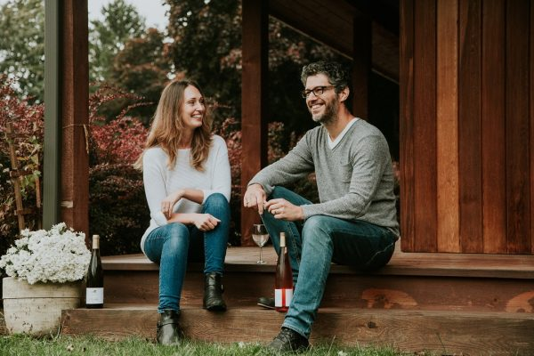 Owners of the Whispering Horse winery sit on wooden steps with bottles of wine