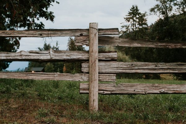 An old wooden fence stands on the property of the Whispering horse winery
