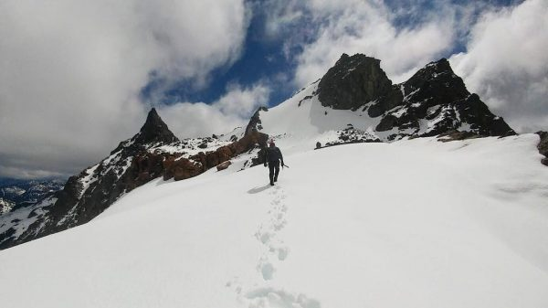 A Person hikes up a snow covered mountain