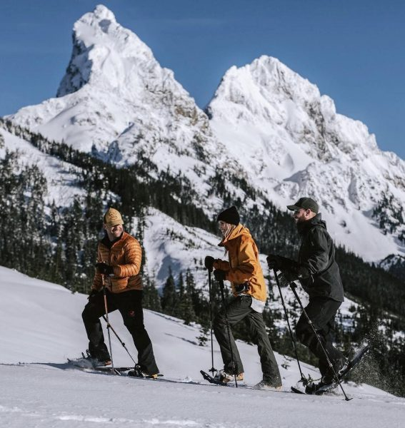 Three people use snowshoes to trek up a snow covered mountain