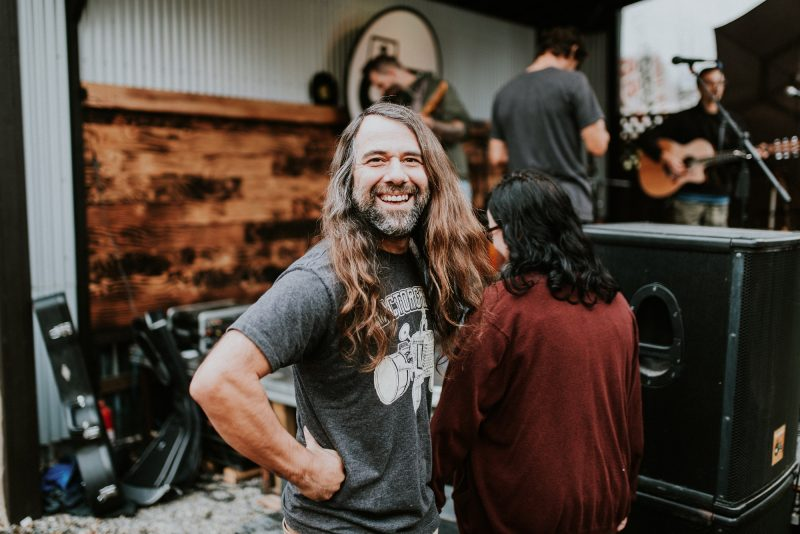 Founder of Tractorgrease cafe smiles for a photo beside the stage