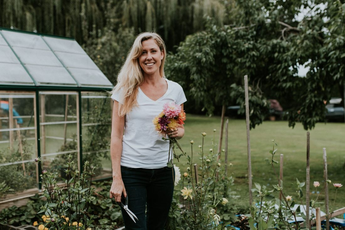 The founder of Rustic Soap holds a bouquet of flowers