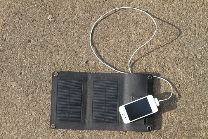 foldable solar panel for travel layed out on the grass charging a smartphone