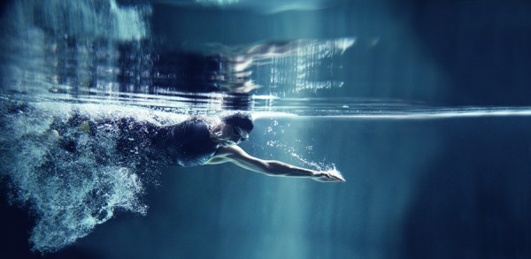 woman swimming underwater intense
