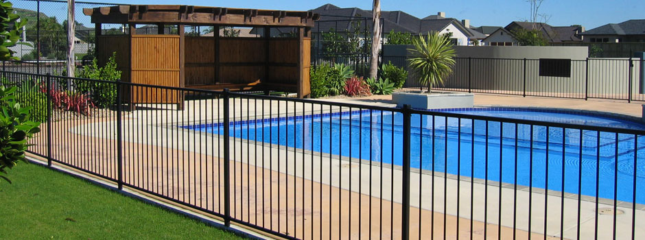 Private outdoor pool with safety fence.