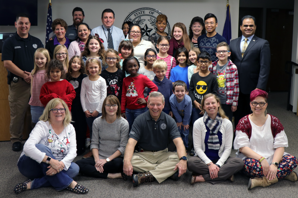 Students form Shady Oaks Elementary School, judge-elect KP George and his chief of staff, Taral Patel, and OEM staff pose for a group photo.