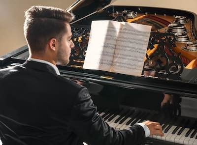 Wedding pianist playing baby grand piano