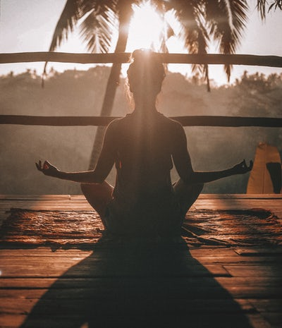 a woman whose back view we have in a meditation pose with her elbows on her knees, facing a sunrise and a palm tree.