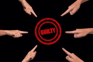 several fingers pointing at the word guilty written in red within two red circles