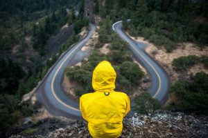 a person in a yellow hoodie facing away from us is watching an empty freeway from a height