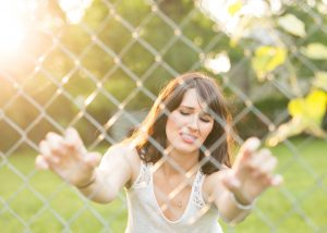woman pushing from inside a chain link fence