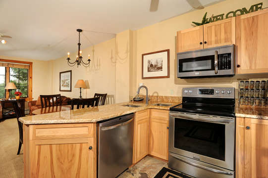 Full kitchen with granite slab counters, double sinks and stainless steel appliances