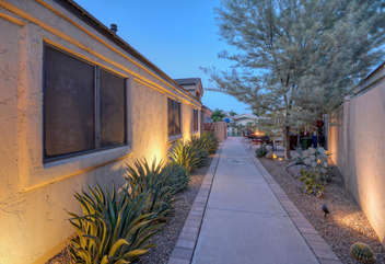 Side entrance to home showcases beautiful landscaping found throughout neighborhood