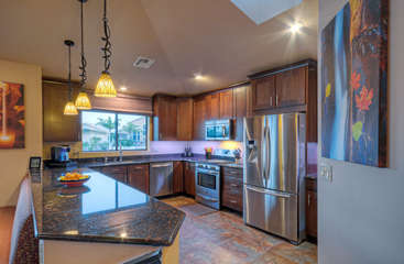 Skylight highlights the beautiful kitchen with granite counters and sumptuous tile floors