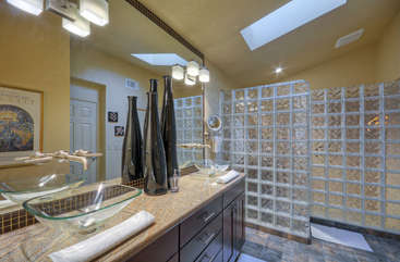 Master bathroom has glass snail shower and two contemporary vanity sinks