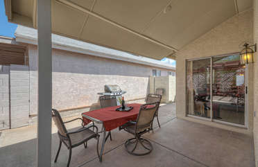 Covered patio with dining furniture and gas grill for outdoor cooking and eating