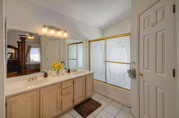 Dual vanity sinks, tub/shower combination and walk-in closet in master bath