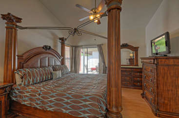 Gorgeous king size canopy bed in master bedroom with patio access
