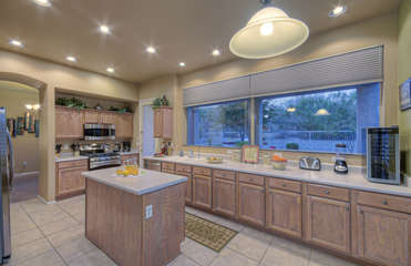 Beautiful custom kitchen with island has large windows that provide natural light and tempting views