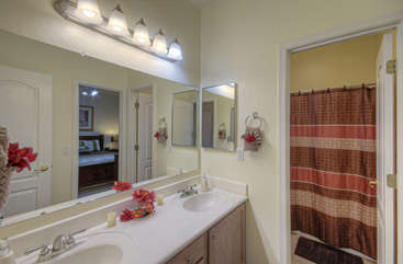 Jack and Jill bathroom between second and third bedrooms has enclosed tub/shower combination and dual vanity sinks