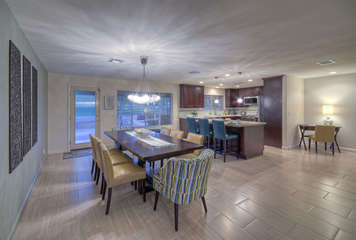 Expansive windows and doors bathe kitchen and dining area in natural light and provide views of backyard oasis