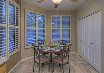Breakfast nook with warm natural lighting seats 4 and has doors to access enclosed laundry area