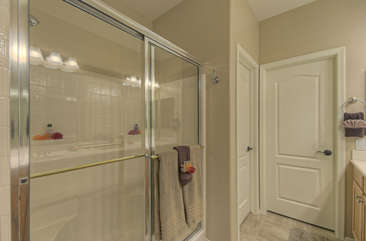 Features of master bath include a walk-in shower and doors to walk-in closet