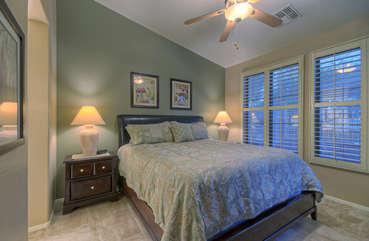 Master bedroom on ground floor has king bed and view of patio and golf course