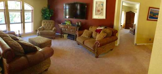 Family room with large windows has wall-mounted television and cozy seating for all